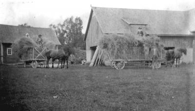 Troligtvis Signe och Husarn på vagnen t.v. och Edward framför vagnen t.h. Personen på lasset (i uniform?) okänd. 1920-talet.